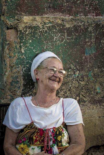 Cuba, Havana, Havana - January 4, 2015: Mature woman laughing in front of a paint splattered wall on the streets of Havana, Cuba