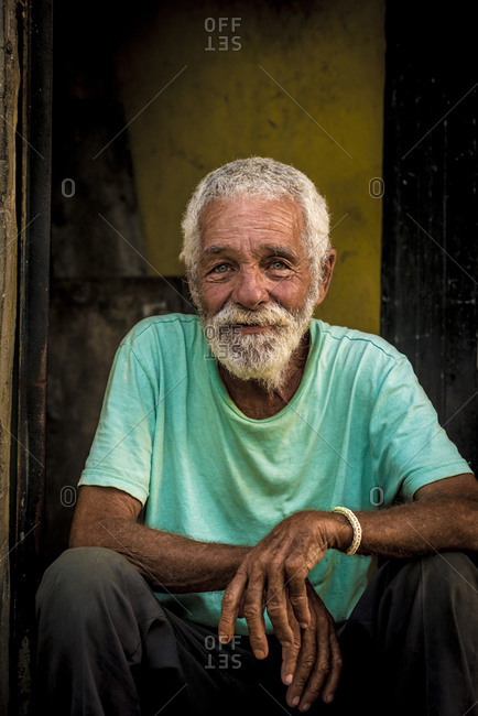 Cuba, Havana, Havana - January 4, 2015: Older man with kind eyes sits smiling in a doorway in Havana, Cuba
