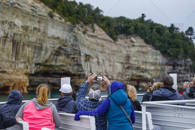 Tourists photographing cliffs at Pictured Rocks National Lakeshore Munising, Michigan, USA
