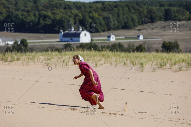 USA, Michigan, Empire - September 21, 2018: Woman running on sand, Empire, Michigan, USA