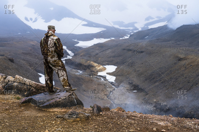 Man looking at volcanic landscape, Mutnovsky, Kamchatka Peninsula, Russia