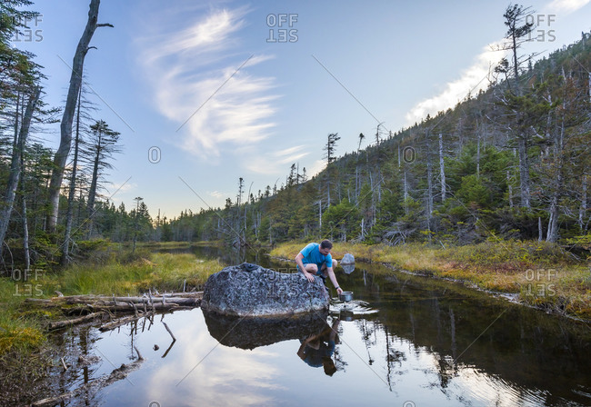 USA, New York, Elk Pass - September 26, 2017: Man taking water from pond, New York, USA