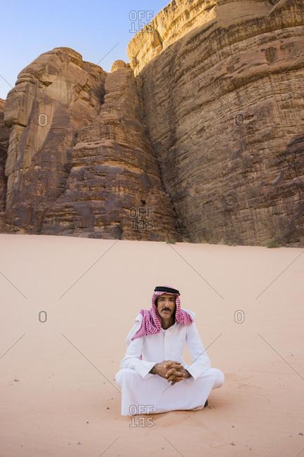 Jordan, Aqaba Governorate, Wadi Rum - October 2, 2016: An Arab man sits in the Wadi Rum desert, wearing traditional Arab clothing