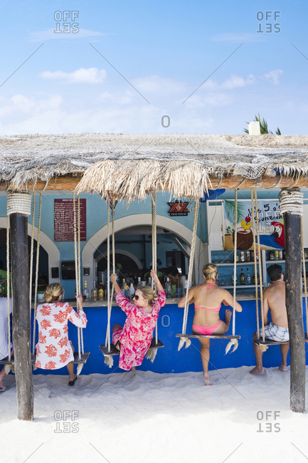 Mexico, Quintana Roo, Tulum - May 3, 2015: People on swings at beach bar, Tulum, Quintana Roo, Mexico