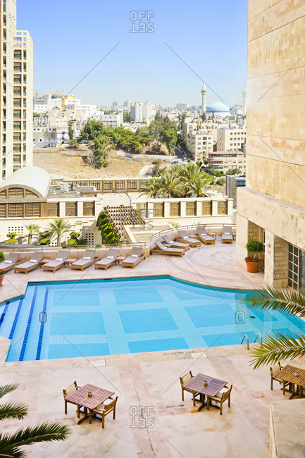 Jordan, Amman Governorate, Grand Hyatt Amman Hotel - September 29, 2016: The rooftop pool deck at the Grand Hyatt Amman, Jordan. Chaise lounges and table and chairs for dining with King Abdullah I Mosque and Amman cityscape in the distance.