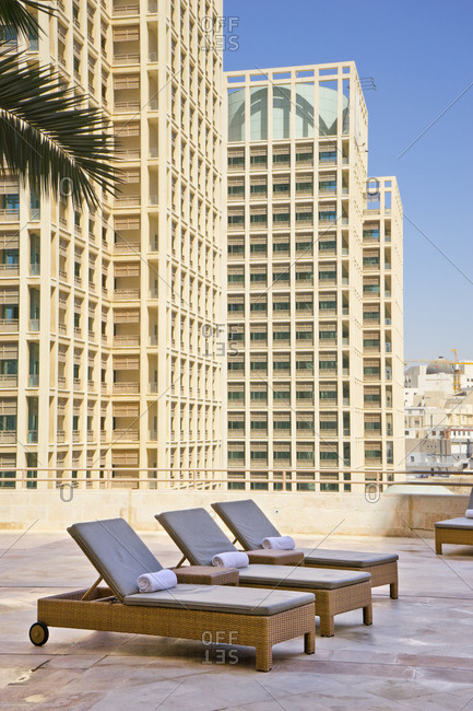 Chaise lounge chairs on a rooftop pool deck with tall city buildings in the background