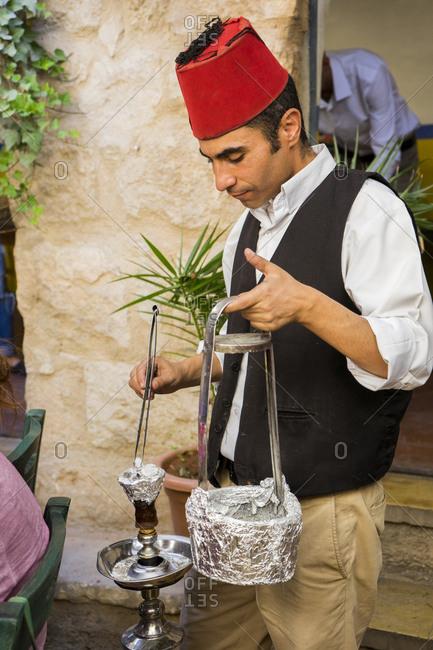 Jordan, Madaba Governorate, Madaba - October 1, 2016: A server wearing a fez puts more coal on a hookah (shisha or sheesha) pipe