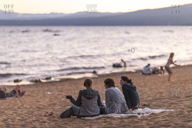 usa, ca, kings beach - July 29, 2011: Three female friends sitting on beach