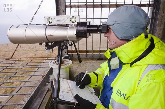 Scotland, Orkney Islands, Stromness - October 26, 2011: Worker looking through binoculars, Stromness, Orkney, Scotland