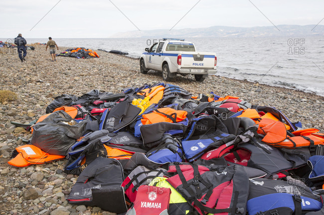 Greece, Lesvos - September 29, 2015: Police car on beach next to pile of life vests abandoned by Syrian migrants, Lesbos, North Aegean, Greece