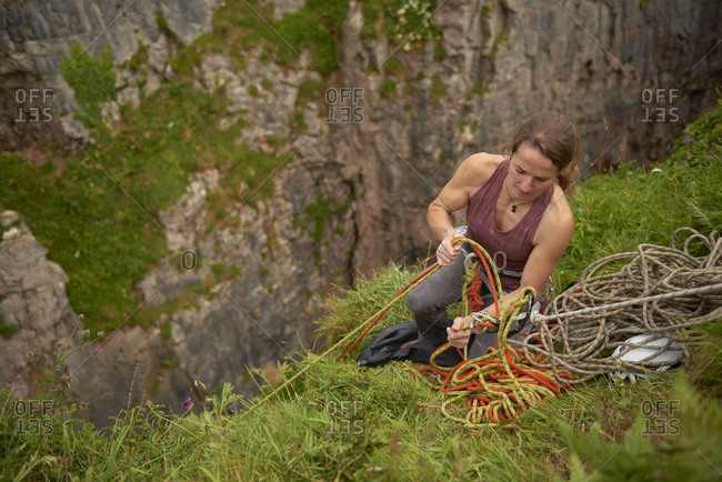 Adventurous female rock climber sitting at the edge of a cliff, Pembroke, Wales, UK