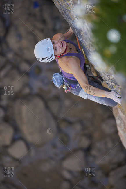View from above of an adventurous woman rock climbing up a cliff, Pembroke, Wales, UK