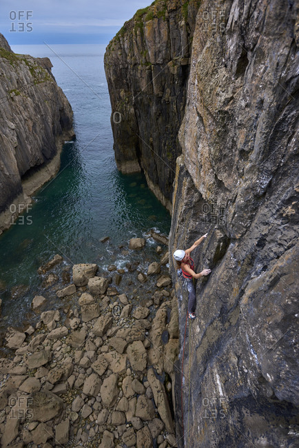 Side view shot of an adventurous woman rock climbing up a cliff on seashore, Pembroke, Wales, UK