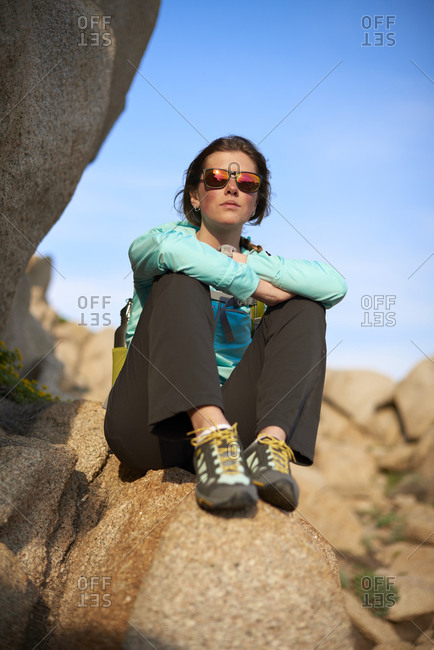 View of young woman sitting on stone, Sardinia, Italy