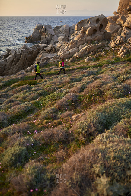 View of couple hiking on rocky coastline, Sardinia, Italy