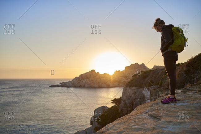 Italy, Sardinia, Capo Testa - April 5, 2017: View of woman standing on cliff by sea, Sardinia, Italy