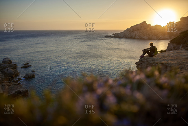 View of woman sitting on cliff by sea, Sardinia, Italy
