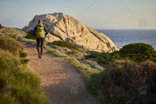 Rear view of woman walking on path on coastline, Sardinia, Italy