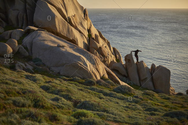 View of man on rocks on coastline, Sardinia, Italy