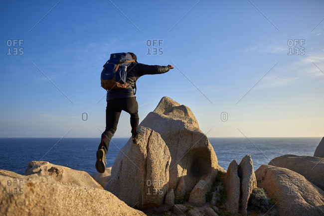 View of man jumping from rock to rock, Sardinia, Italy