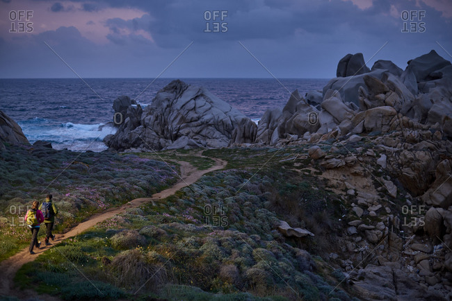 View of couple walking down path on coastline, Sardinia, Italy