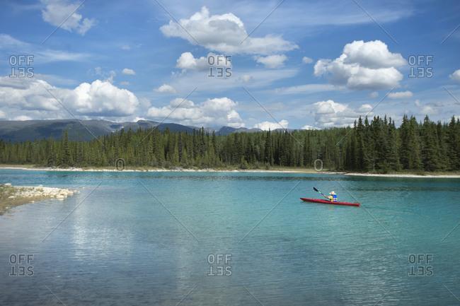 View of man canoeing in lake, British Columbia, Canada