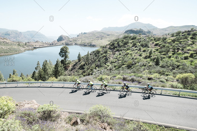 Spain, Canary Islands, Gran Canaria - March 25, 2018: Group of people cycling along road, Gran Canaria, Canary Islands, Spain