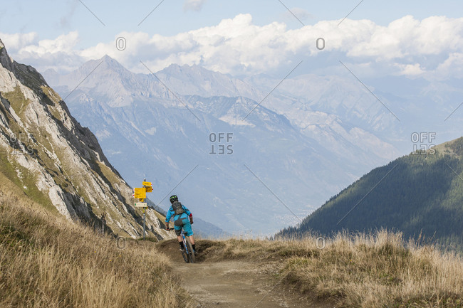 Mountain biker on dirt road in mountains, Chamonix, Haute-Savoie, France