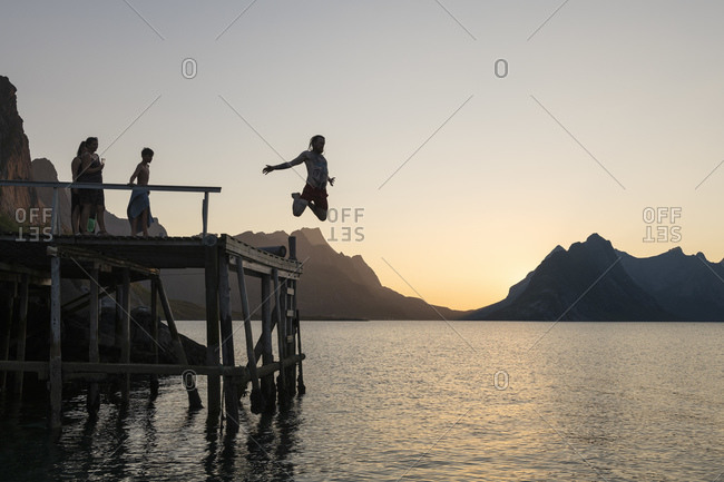 Norway, Lofoten Islands, Reine - July 28, 2018: Person jumps from wooden pier into Reinefjord on summer evening, Muskiness �y, Lofoten Islands, Norway