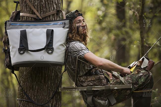 Deer hunter with bow and arrow waiting, Bear Creek Reserve, Georgia, USA