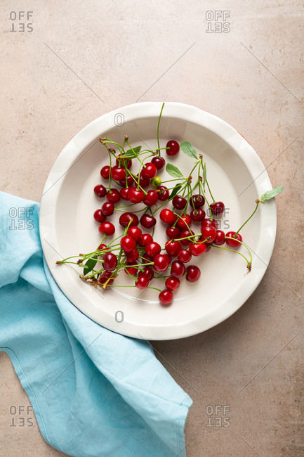 Overhead view of fresh cherries in baking dish and blue linen