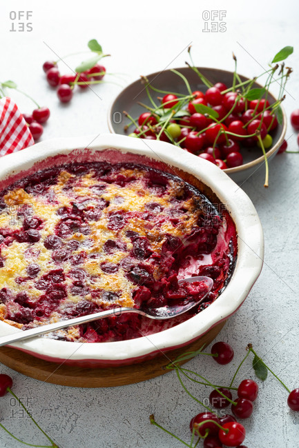 Close up of cherry clafoutis and cherries on light surface
