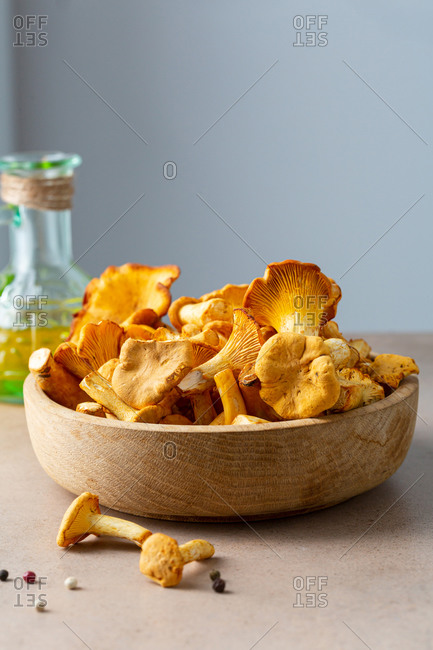 Chanterelles mushrooms in wooden bowl on stone table