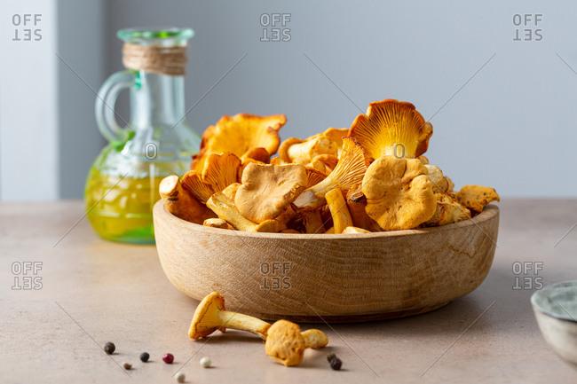 Chanterelles mushrooms in wooden bowl close up