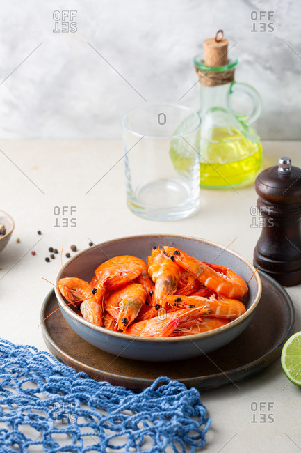 Shrimps in bowl on light table by oil and pepper