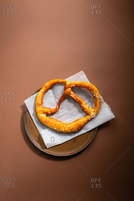 Overhead view of a salty pretzel on brown plate