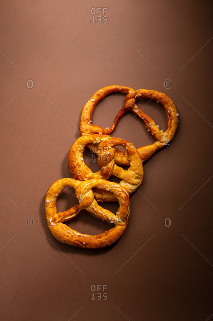 Overhead view of salty pretzels on brown background