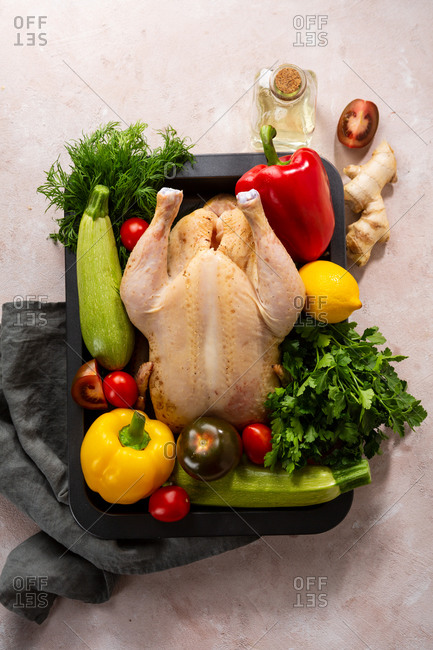 Overhead view of a whole raw chicken with fresh vegetables