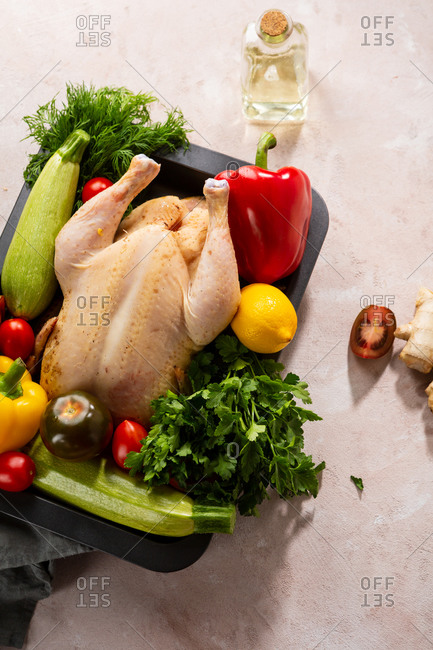 Top view of a whole raw chicken with fresh vegetables