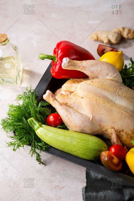 Close up of a raw whole chicken with fresh vegetables
