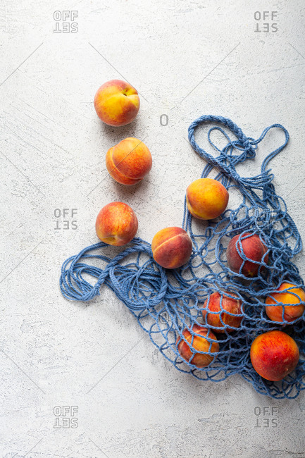 Overhead view of peaches in a blue net bag on light surface