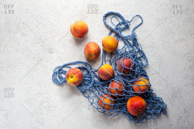 Peaches in blue eco net bag on light surface
