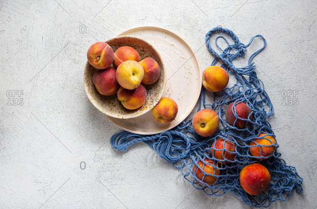 Overhead view of peaches on plates and in net bag