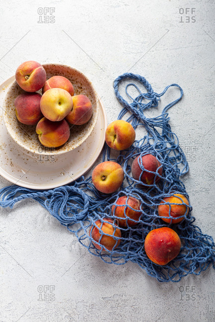 Overhead view of peaches on plates and in eco net bag on light surface