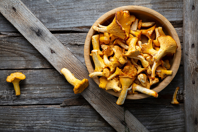 Overhead view of chanterelles mushrooms in bowl on rustic surface