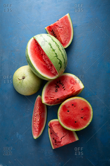 Overhead view of sliced melons on blue background