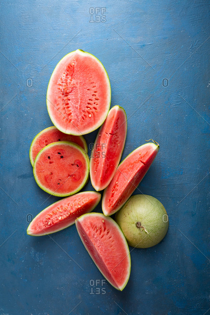 Overhead view of slices of cut ripe watermelons on blue surface