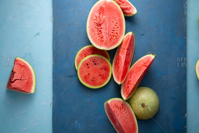 Slices of ripe watermelons on two-toned blue surface