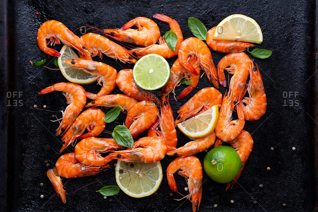 Overhead view of prawn with lime and spices on black tray