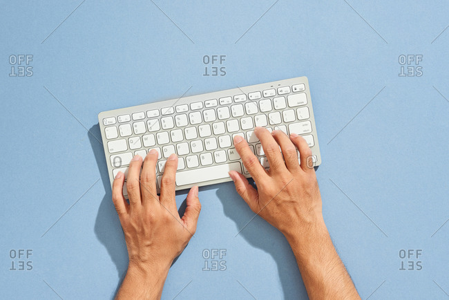 Hands typing computer keyboard viewed from above
